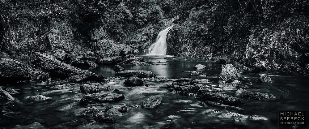 A panoramic monochrome photograph of a waterfall in Crystal Cascades, Far North Queensland.<br /> <br /> Code: CAQT0019<br /> <br /> Limited Edition of 5 Prints