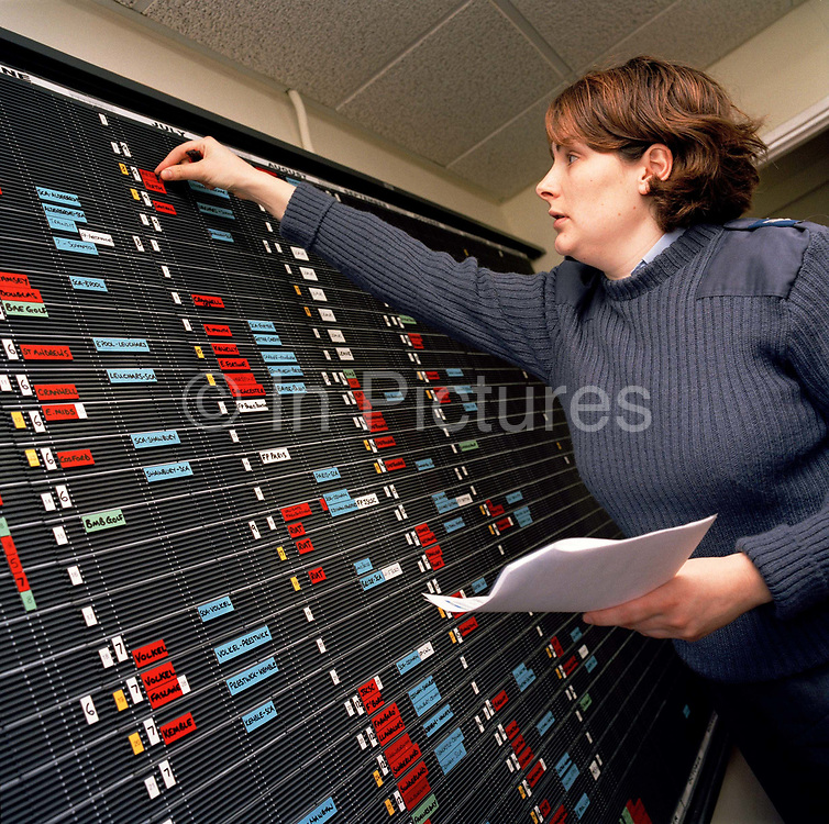 Corporal Karen McNally is a flight planning administrator in the 'Red Arrows', Britain's Royal Air Force aerobatic team. Reaching up across the information board, this RAF lady is responsible for maintaining this vital part of the team's logistical plans that are outlined on this busy calendar of their movements and appearances at a seasonal series of air shows and fly-pasts across the UK and a few European venues. Since 1965 the squadron have flown over 4,000 shows in 52 countries and are an important part of Britain's summer events where aerobatics aircraft perform their manoeuvres in front of massed crowds. Corporal McNally is a part of the team called the Blues, the team's ground support personnel that outnumber the pilots (the Reds) by 8 to 1.
