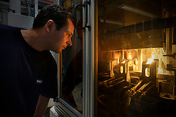 Gert Gooris, a Philips technician, monitors one of the robotic machines during the ceramic metal halide lamp manufacturing process, at the Philips Lighting factory, in Turnhout, Belgium, on Friday, Oct. 15, 2010. (Photo © Jock Fistick)