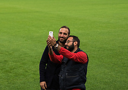December 4, 2017 - Piraeus, Greece - Gonzalo Higuaín with a fan during a walk around at Karaiskaki stadium on the eve of their UEFA Champions League group D match against Olympiakos Piraeus  (Credit Image: © Dimitris Lampropoulos/NurPhoto via ZUMA Press)