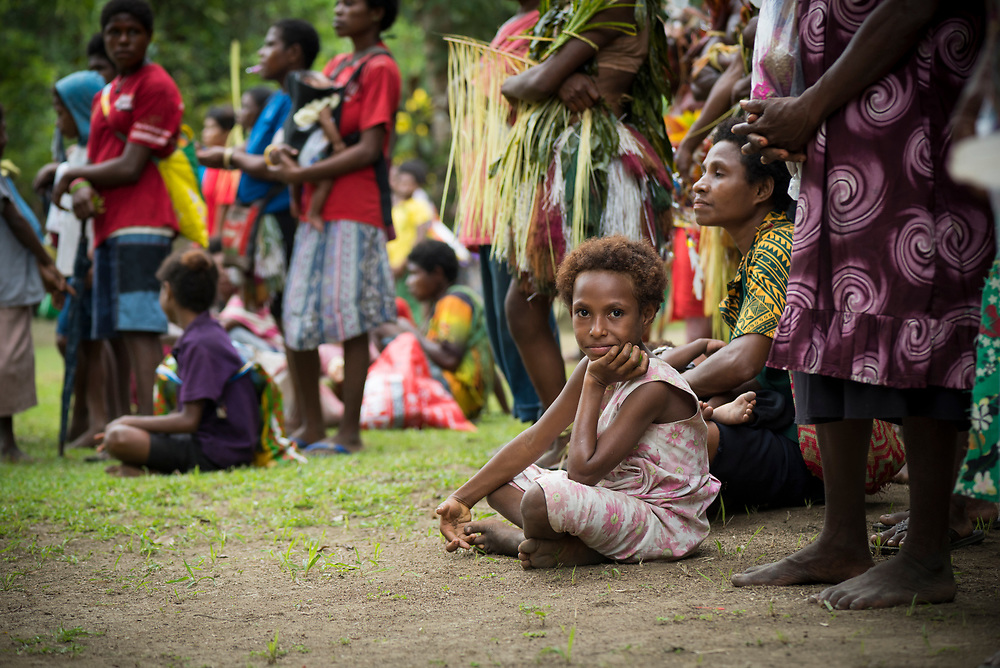 A young girl sits on the ground during a celebration in Tambapmining, a village on the lower Ramu River in Madang Province, Papua New Guinea (2017)