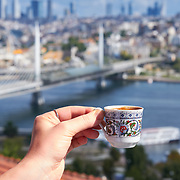 Hand holding cup of turkish coffee with panoramic view of Golden Horn, Istanbul, Turkey