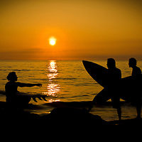 A group of surfers sit and wait patiently for the tide to change and bring on the surf in the Equatorial town, Montanita.