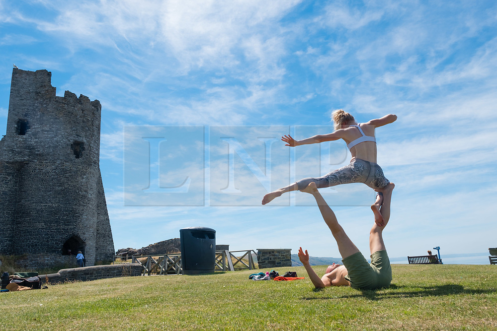 © Licenced to London News Pictures<br /> 25 June 2018 . Aberystwyth Wales UK<br /> UK Weather: A very fit young couple practice their Acro Yoga ( a mix of acrtobatics and yoga) near the castle  in Aberystwyth, on yet another scintillating day of hot unbroken sunshine.<br /> The UK is heading  into a mini heatwave, with temperatures forecast to hit 29º or 30º Celsius by the middle of the week<br /> photo credit Keith Morris / LNP