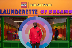 © Licensed to London News Pictures. 27/10/2021. LONDON, UK.  Award-winning artist and designer Yinka Ilori unveils his 'Launderette of Dreams', a new installation where he has reimagined a community launderette in his signature colourful style. Made from over 200,000 LEGO bricks, the installation forms part of the LEGO Group's Rebuild the World campaign that celebrates children as masters of creative problem solving.  It can be found in Bethnal Green Rd, Shoreditch, 28 October to 6 November 2021..  Photo credit: Stephen Chung/LNP