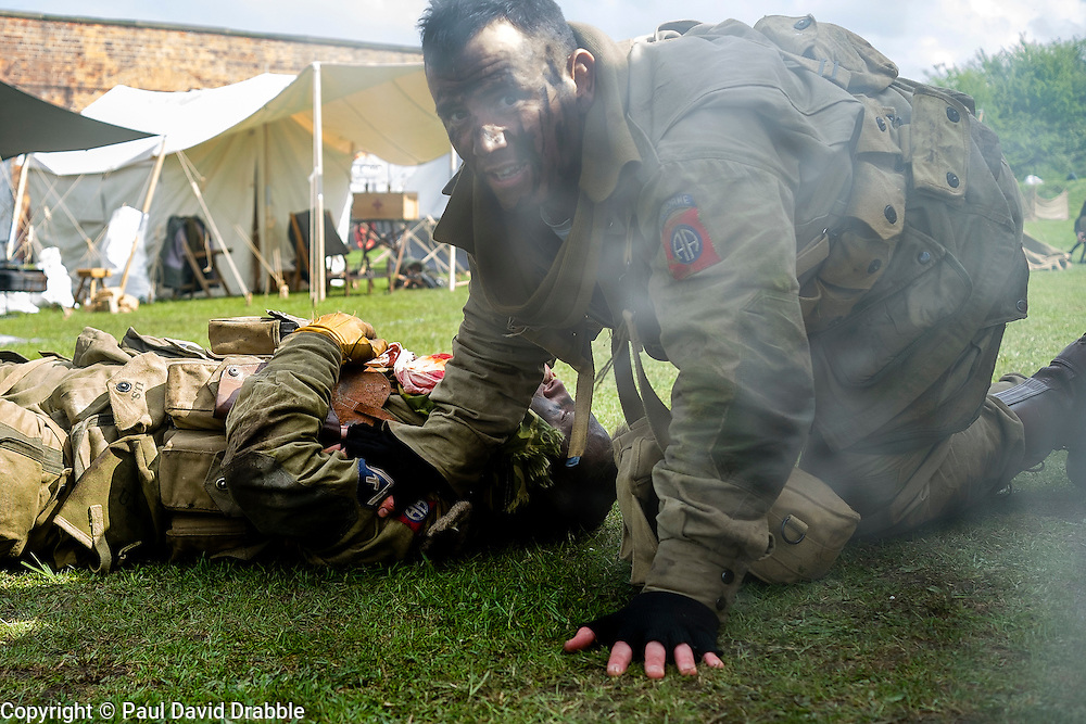 """Members of the US 82nd Airborne/505th RCT living History Group take part in the first days battle re-enactment at Fort Paull one reenactor beside a """"battlefield casualty"""" he has just dragged out of the line of fire<br /> <br />   03 May 2015<br />   Image © Paul David Drabble <br />   www.pauldaviddrabble.co.uk"""