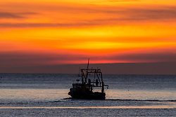 © Licensed to London News Pictures. 25/03/2018. Scarborough UK. A fishing boat leaves Scarborough harbour at sunrise this morning on the Yorkshire coast. Photo credit: Andrew McCaren/LNP