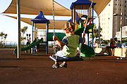 Smiling young girl of two on a swing in a playground