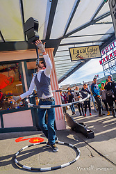 A sidewalk entertainer balances a guitar while spinning a hoop near the Pike Place Market in downtown Seattle, Washington.
