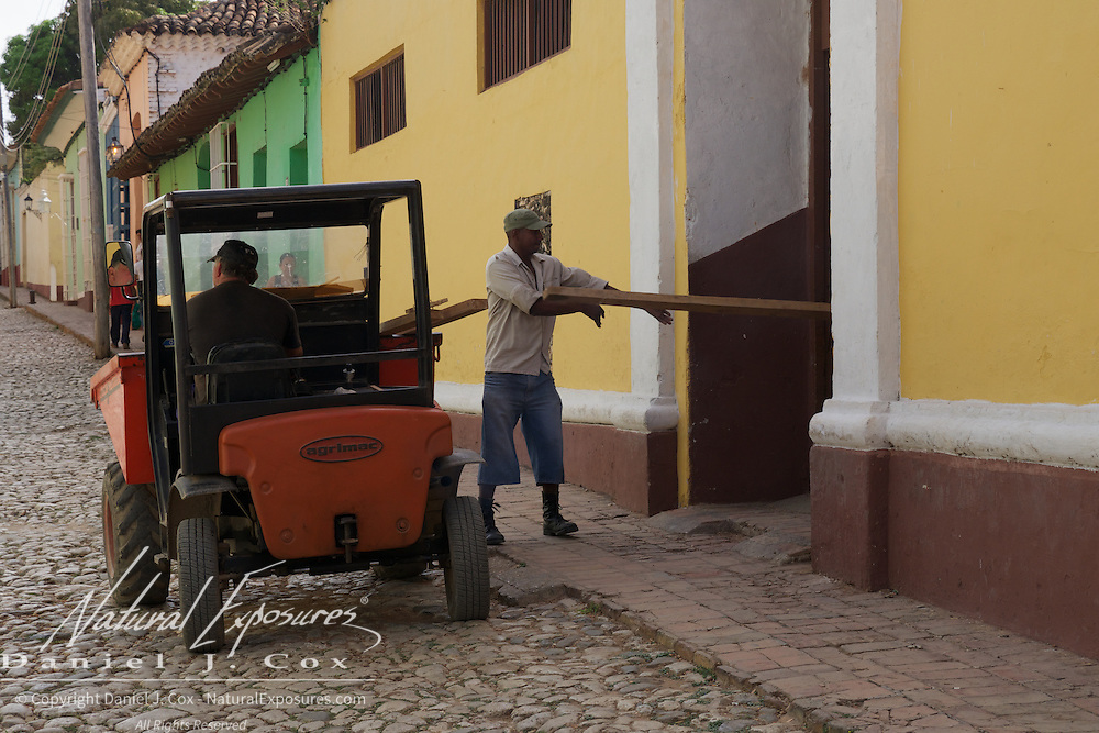 A local man unloads wood from a cart in Trinidad, Cuba.