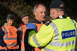 A Surrey Police officer monitors Insulate Britain climate activist Reverend Tim Hewes after both carriageways of the M25 were blocked by activists between Junctions 9 and 10 on 21st September 2021 in Ockham, United Kingdom. Insulate Britain are demanding that the government immediately promises both to fully fund and ensure the insulation of all social housing in Britain by 2025 and to produce within four months a legally binding national plan to fully fund and ensure the full low-energy and low-carbon whole-house retrofit, with no externalised costs, of all homes in Britain by 2030.