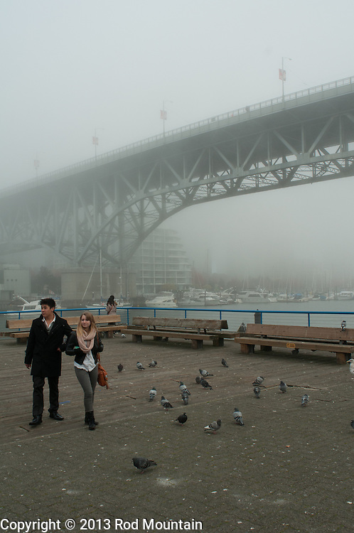 A young couple walking on Granville Island. In the distance, the city of Vancouver is shrouded in Fog.