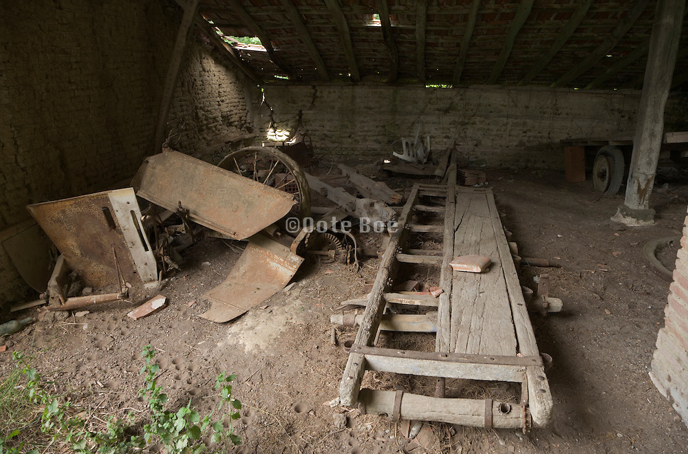 old abandoned barn with dilapidated farming equipment