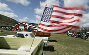 """The American flag flies from the bed of """"Old Yeller,"""" a 1959 Chevy Apache pickup. In the background is the new Eastern Washington Agricultural Museum. <br /> Alan Berner / The Seattle Times"""