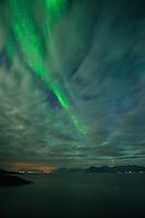 Northern Lights - Aurora Borealis emerge from behind clouds, near Henningsvær, Austvågøy, Lofoten Islands, Norway