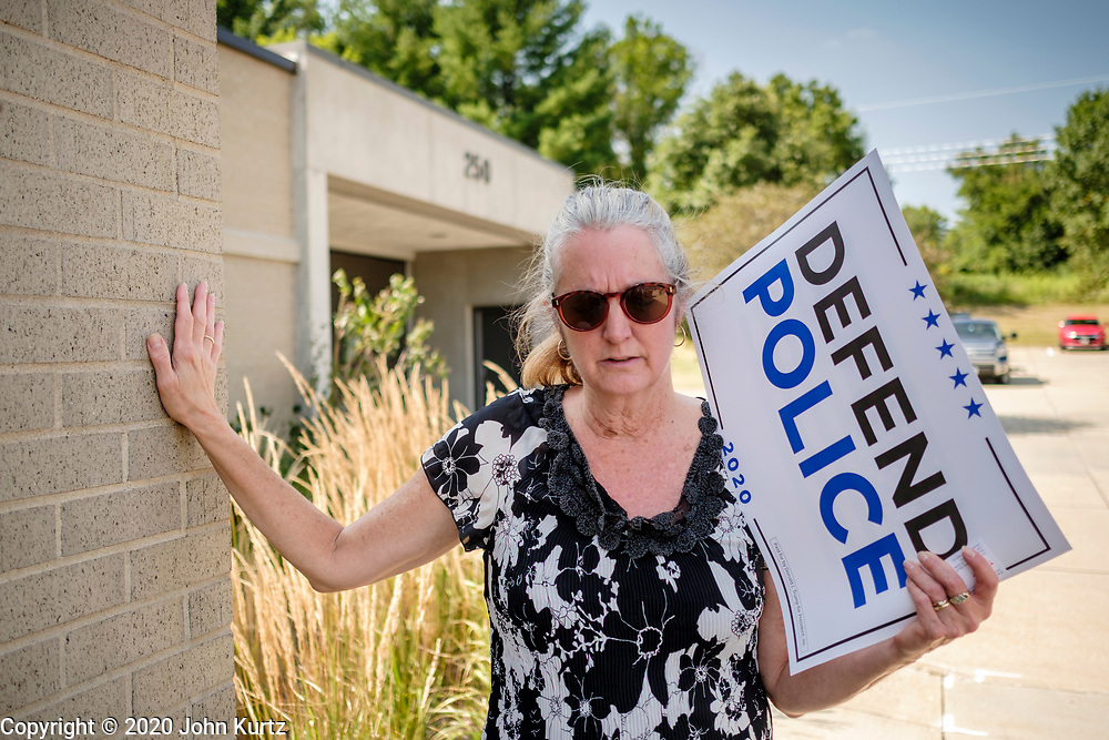 """08 AUGUST 2020 - WEST DES MOINES, IOWA: A woman touches the West Des Moines Law Enforcement Center while she prays for police officers after a rally to support police and law enforcement in West Des Moines. About 100 people gathered at the West Des Moines Law Enforcement Center to rally in support of law enforcement. The rally was organized by """"Uplifting Our Police,"""" a local organization that supports law enforcement. They rallied at Des Moines Police headquarters in July. They are planning similar rallies at police stations in the Des Moines metropolitan area.     PHOTO BY JACK KURTZ"""
