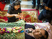 27 JANUARY 2014 - BANGKOK, THAILAND: A woman participates in the bathing rites for anti-government leader Suthin Taratin at Wat Sommanat Rajavaravihara in Bangkok. In Thai tradition, after death a bathing ceremony takes place in which relatives and friends pour water over one hand of the deceased. Suthin was a core leader of the People's Democratic Force to Overthrow Thaksinism (Pefot), one of several organizations leading protests against the elected government of Thai Prime Minister Yingluck Shinawatra. He was murdered Sunday, Jan. 28, while he was leading a rally to prevent voters from reaching a polling center in the Bang Na district of Bangkok.     PHOTO BY JACK KURTZ