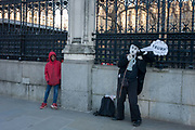 Outside Britains Palace of Westminster parliament, a young black boy looks sideways at a Charlie Chaplin character making a Donald trump joke, on the day of Trumps inauguration as the 45th US president, on 20th January, in Parliament Square, London borough of Westminster, England.