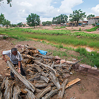 """080213       Brian Leddy<br /> Wilbur Haluacwa piles wood on his property next to the Zuni River in Zuni on Friday. Haluacwa, who has lived at the location for about 30 years has not seen the river flow in a long time. """"It's been too long, probably at least 20 years,"""" he said."""