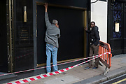 """Workmen on a shop refit on Bond Street, London, England, UK. Most exclusive shopping district in upmarket Mayfair. It has been a fashionable shopping street since the 18th century. Technically """"Bond Street"""" does not exist: The southern section is known as Old Bond Street, and the northern section, is known as New Bond Street. The rich and wealthy shop here mostly for high end fashion and jewellery."""