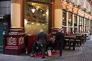 City businessmen have their shoes shined in Leadenhall Market, a few days before Christmas.