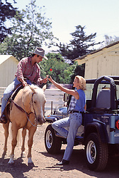 cowboy on a horse giving a rose to a woman leaning against a jeep on a ranch