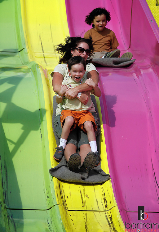 Kevin Bartram   Staff<br /> Nanci Hyburg and Skylar Hyburg, 5, are followed by Dylan Hyburg, 7, as the family from Berlin goes down the giant slide during the first day of the Berlin Fair on Friday. The fair continues through Sunday and features a variety of rides, shows and displays.
