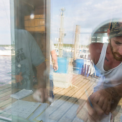 Ryan Schultz records a transaction at the Friendship Lobster Co-op in Friendship, Maine.