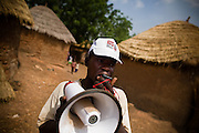A community volunteer uses a megaphone to announce an upcoming national polio immunization campaign in the village of Gbulahabila, northern Ghana on Wednesday March 25, 2009..