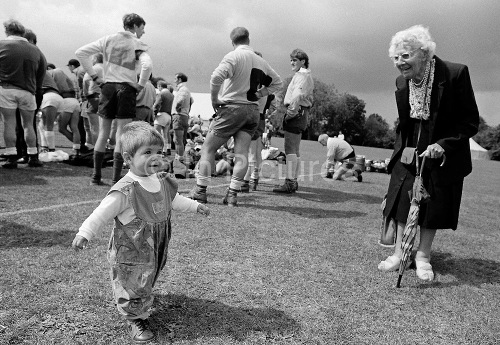 """""""Crooked Lady."""" A twelve month-old girl who has recently learned to walk proudly strides past an elderly lady with balancing arms outstretched while at the Dulwich Show in South London. There is a marked difference between the youthful, upright posture of the young girl to the hunched and bent stance of the old woman who stands supporting herself on a brolley. It is a picture that compares youth with old age, the delight that a person of later years shows to a child whose life reaches far ahead. This is from a documentary series of pictures about the first year of the photographer's first child Ella. Accompanied by personal reflections and references from various nursery rhymes, this work describes his wife Lynda's journey from expectant to actual motherhood and for Ella - from new-born to one year-old."""