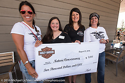 Harley-Davidson employees Jodi Searle and Manon Durand hand over a check for $2,000 to the Nature Conservancy after the Harley-Davidson Women's Angels Ride during the annual Sturgis Black Hills Motorcycle Rally.  SD, USA.  August 12, 2016.  Photography ©2016 Michael Lichter.