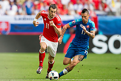BORDEAUX, FRANCE - Saturday, June 11, 2016: Wales' Gareth Bale competes with Slovakia's Jan Durica in the match during the UEFA Euro 2016 Championship at Stade de Bordeaux. (Pic by Paul Greenwood/Propaganda)
