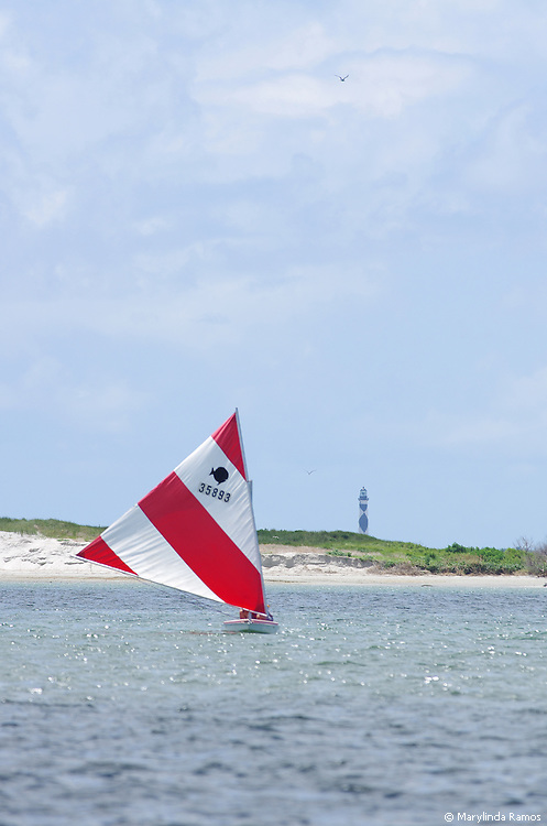 Sunfish sailing with Cape Lookout in the background.