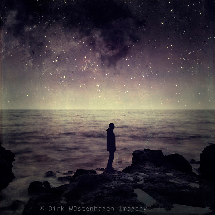 Silhouette of a man standing at the ocean at night.<br /> Composing made with my own photos