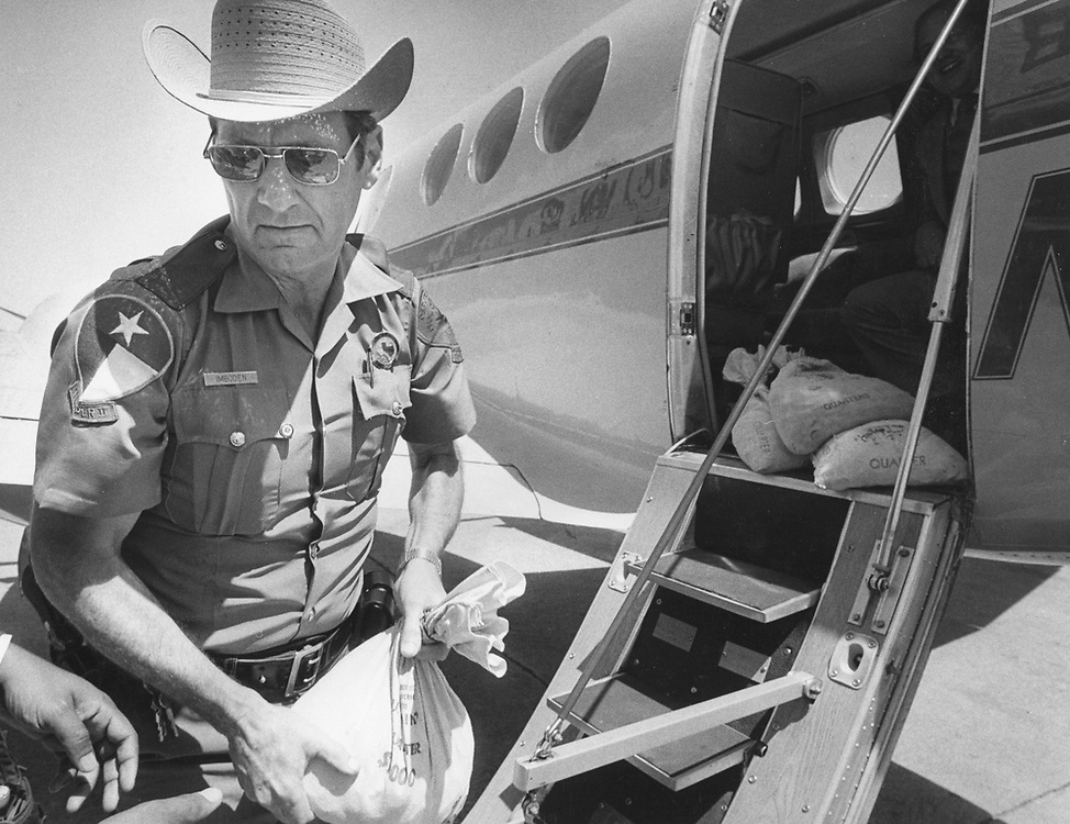 ©1991 Texas DPS officer unloads bags of coins that were confiscated in a drug and gambling raid with white collar crime.