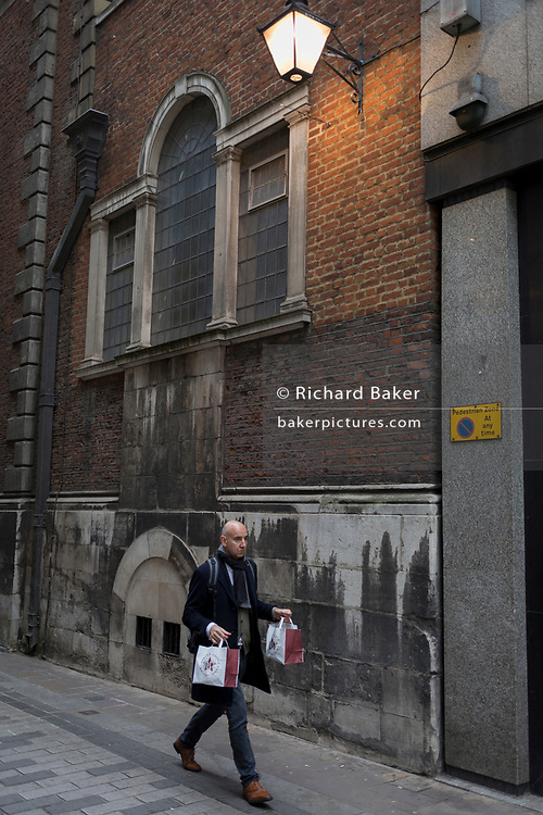 A man carries two Pret a Manger lunch bags down Bow Lane in the City of London, the capital's financial district and oldest district, on 22March 2019, in London, England.