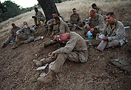 A Marine uses baby-wipes to clean up while others eat MRE's after waiting for hours for the day's live-fire exercises to take place -- something that didn't happen until the next day for the 2nd Battalion, 5th Marine Regiment due to federally protected bison on the range at Camp Pendleton.<br /> <br /> <br /> ///ADDITIONAL INFO:   <br /> <br /> david.marines.0705.kjs  ---  Photo by KEVIN SULLIVAN / Orange County Register  --  6/28/13<br /> <br /> Live-fire exercises by the United States Marine Corps' 2nd Battalion, 5th Marine Regiment  (2/5) based out of Marine Corps Base Camp Pendleton, California. The 2/5 fall under the command of the 5th Marine Regiment and the 1st Marine Division.<br /> <br />   6/28/13.