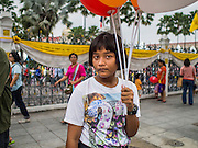 10 JANUARY 2015 - BANGKOK, THAILAND: A child waits to cross a Bangkok street during celebrations at Government House in Bangkok. National Children's Day falls on the second Saturday of the year. Thai government agencies sponsor child friendly events and the military usually opens army bases to children, who come to play on tanks and artillery pieces. This year Thai Prime Minister General Prayuth Chan-ocha, hosted several events at Government House, the Prime Minister's office.    PHOTO BY JACK KURTZ