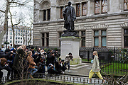 As if posing on an outdoor catwalk, a young fashionista woman walks towards cameras gathered outside the The National Portrait Gallery where a statue to the actory Henry Irving (1838-1905) looks down on the frenzied procedings, during London Fashion Week, on 17th February 2020, in London, England.