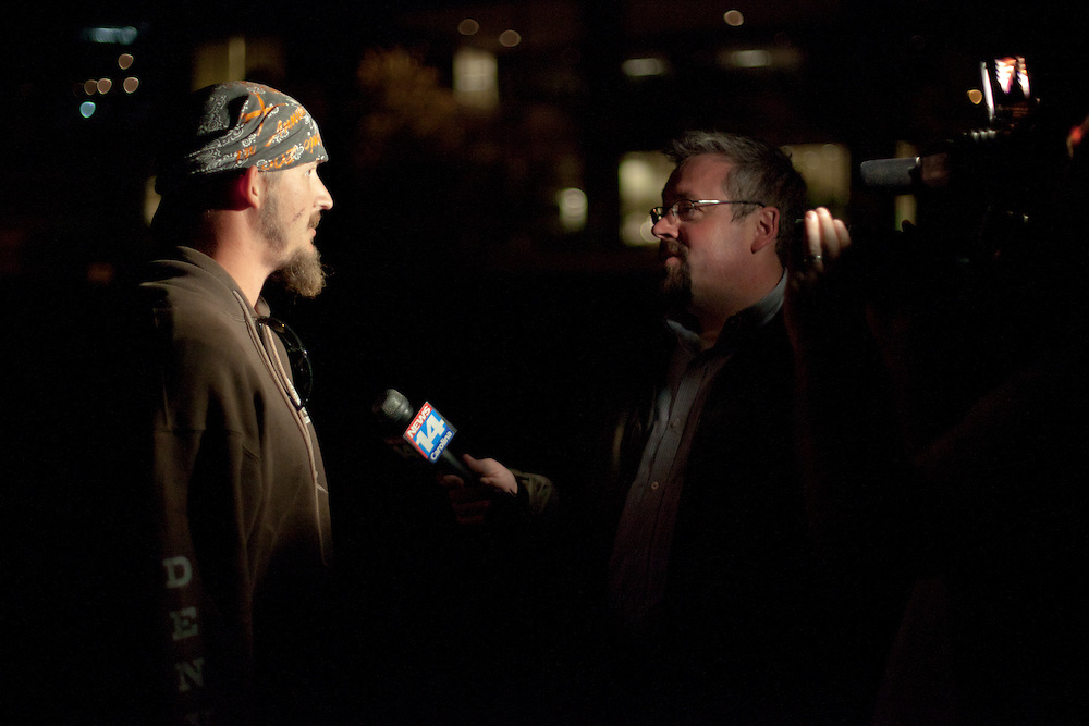 A union welder gets interviewed by the local news as members of Occupy Charlotte set up camp.
