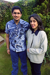 Single mother standing in garden with teenage son smiling,