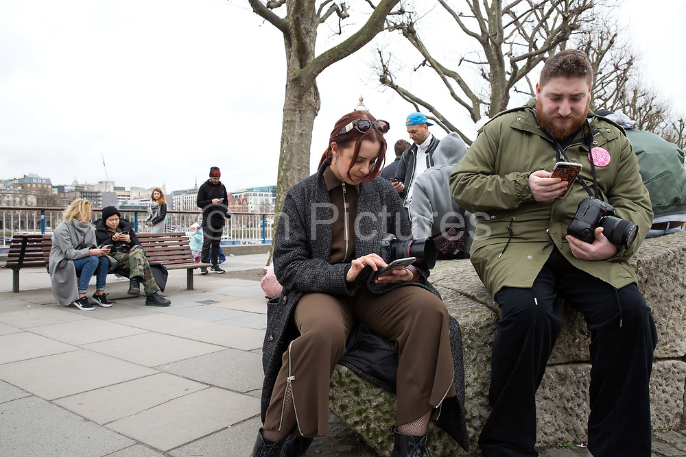 During London Fashion Week, outside The National Theatre, various people use their mobile phones on 19th February 2017 in London, United Kingdom. From the series Our Small World, an observation of our mobile phone obsessions