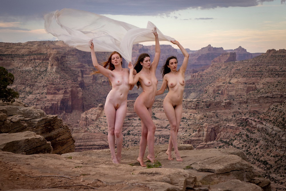 Three nude women, facing the camera, holding gauze above their heads, and standing at the top of a cliff in the <br /> Little Grand Canyon, Utah