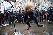 Heavy metal guitarist plays his guitar solo on Whitehall during a demo in London, England, United Kingdom. Playing thrash style music and leaping around in a kind of music ecstacy to the delighted gathered crowd.