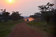 Range Rover safari vehicle  at sunset on dirt road in Tanzania, Africa