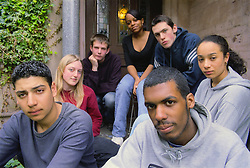 Multiracial group of teenage boys and girls sitting outdoors on doorstep,