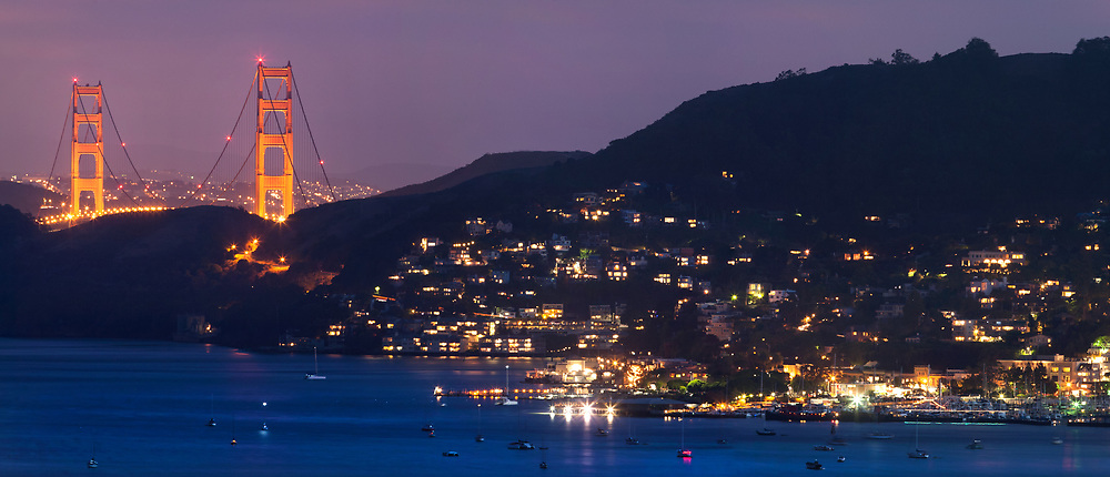 Sausalito and the Golden Gate Bridge shine at dusk. As seen from across Richardson Bay at the hippie tree.
