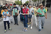 Asian tourists in Westminster in London, England, United Kingdom. Some South East Asian tourists travel in large tour groups and is especially noticable as tourism levels increase.