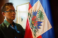 United Nations Protocol Assistant Gavin Pan, holds the national flag of Haiti, on the 38th floor of the United Nations.