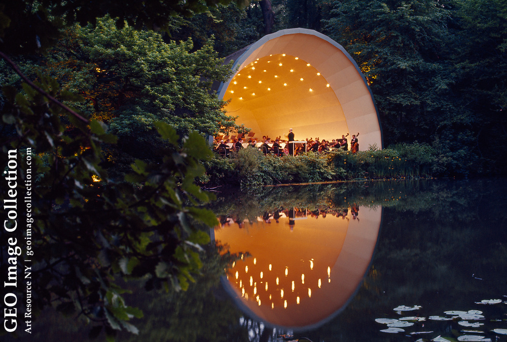 Orchestra plays beneath stars in orchestra shell reflected on lake.
